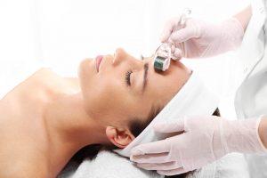 Especialista realizando procedimento de microagulhamento em uma mulher | Microagulhamento