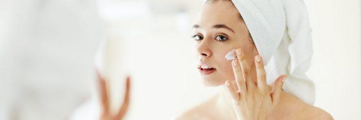 Mulher na frente do espelho passando creme facial | Como amenizar marcas de acne