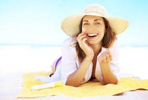 Mulher sorrindo com chapéu de Sol passando protetor solar na praia | Mulher sorrindo e brincando com cabelo na praia | Cuidados com pele para o verão
