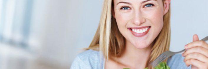 Mulher sorrindo e comendo salada | Os benefícios da alimentação saudável para a pele