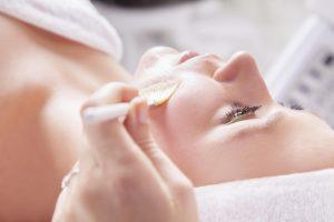 Mulher deitada com profissional fazendo peeling | Tratamentos