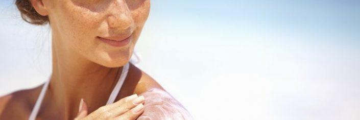 Mulher na praia passando protetor | Como evitar o câncer de pele?