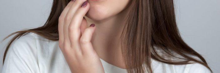 Menina com herpes na boca tocando a ferida