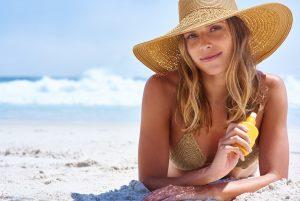 Mulher deitada de frente na areia da praia com protetor solar nas mãos e chapéu