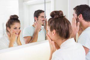 Homem e mulher olhando no espelho passando produtos na pele