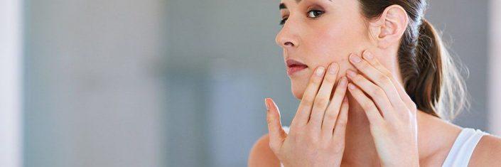 Mulher adulta olhando o rosto com acne no espelho